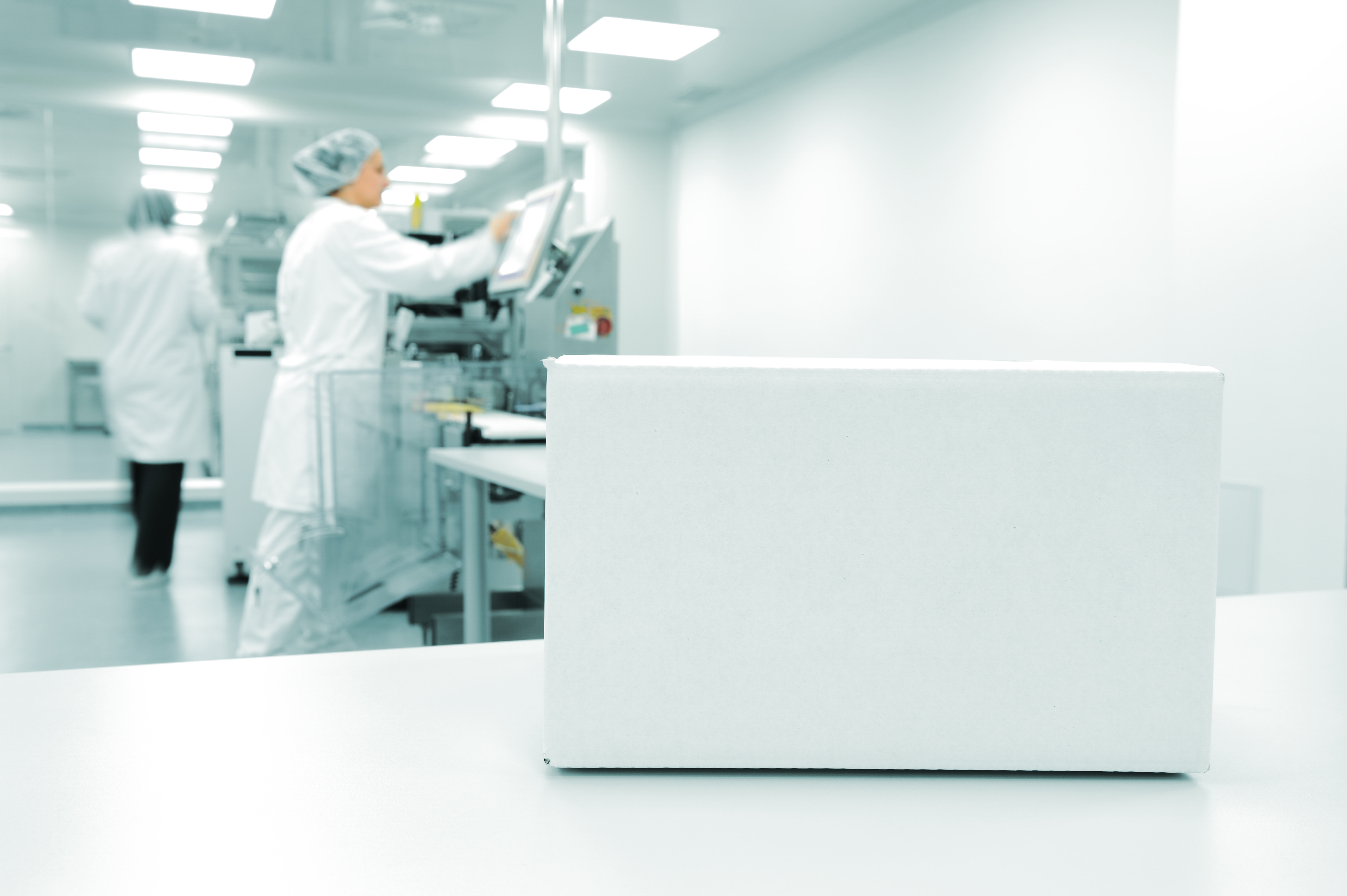 White box at automated production line at modern factory, people worki